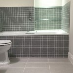 An 1800 bath with a tiled panel in green mosaic