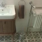 An oak basin unit with patterned floor tiles