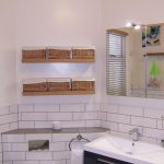 Bathroom picture with floating oak shelves and wicker baskets.