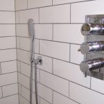 Picture of a recessed thermostatic shower valve wth three handles.