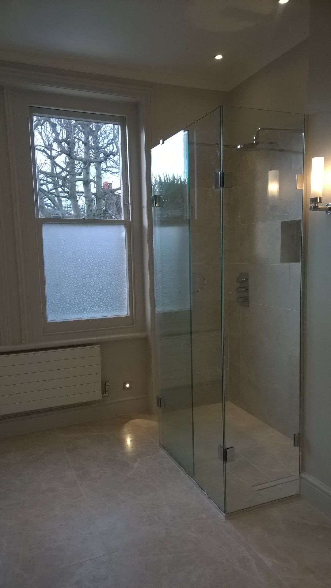 A wetroom shower area with shwoer screen and recessed shower valve