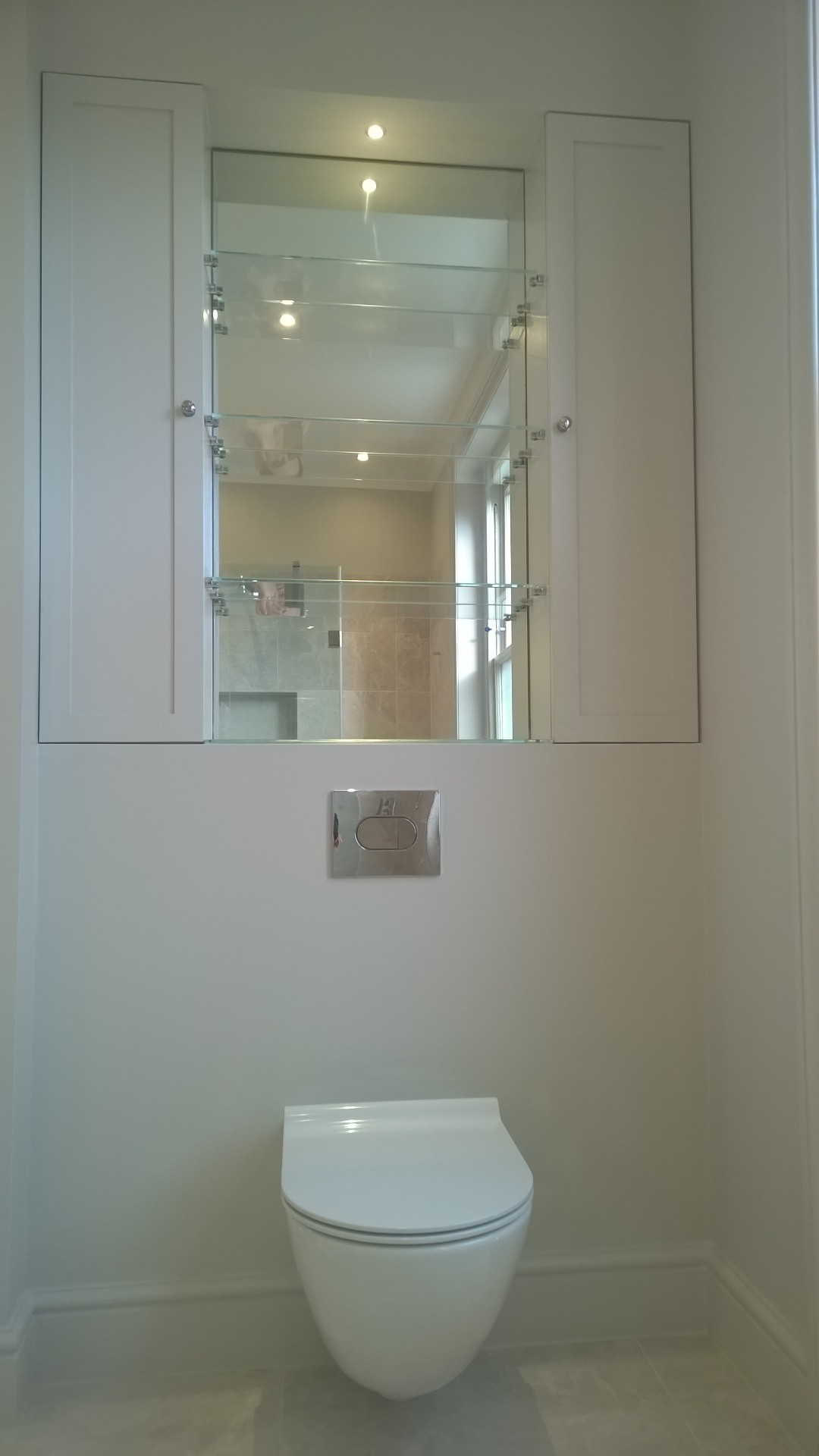 A wall hung WC with bespoke mirror cabinets and shelves above