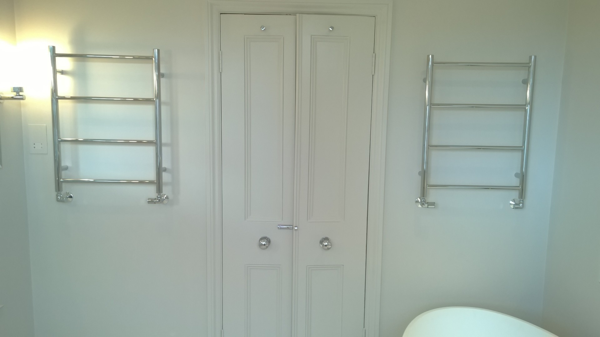 Double doors into a bathroom with heated towel rails