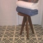 Wooden stool with folded towels on a floor with patterened floor tiles