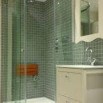 Off set quarant shower with a fold away wooden shower seat