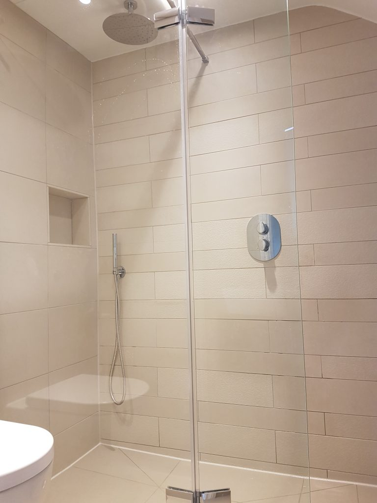A bathroom picture shower a wet room with textured porcelain wall tiles and impey aqua dec shower tray