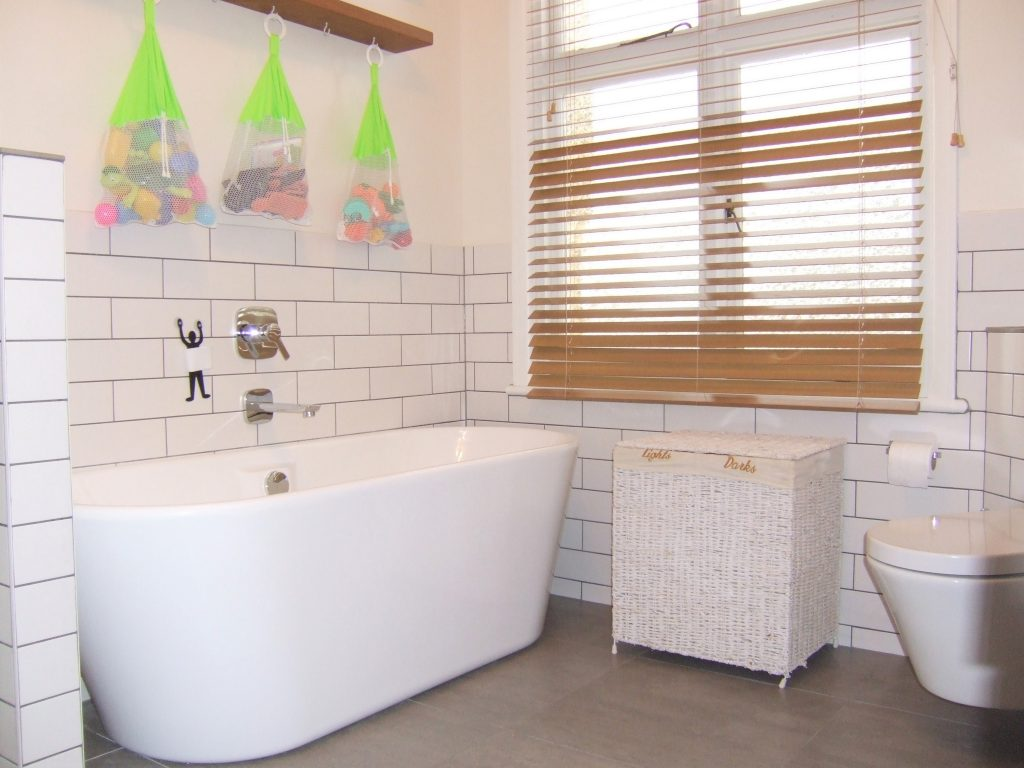 Picture of a bathroom with freestanding bath and metro wall tiles with grey grouting