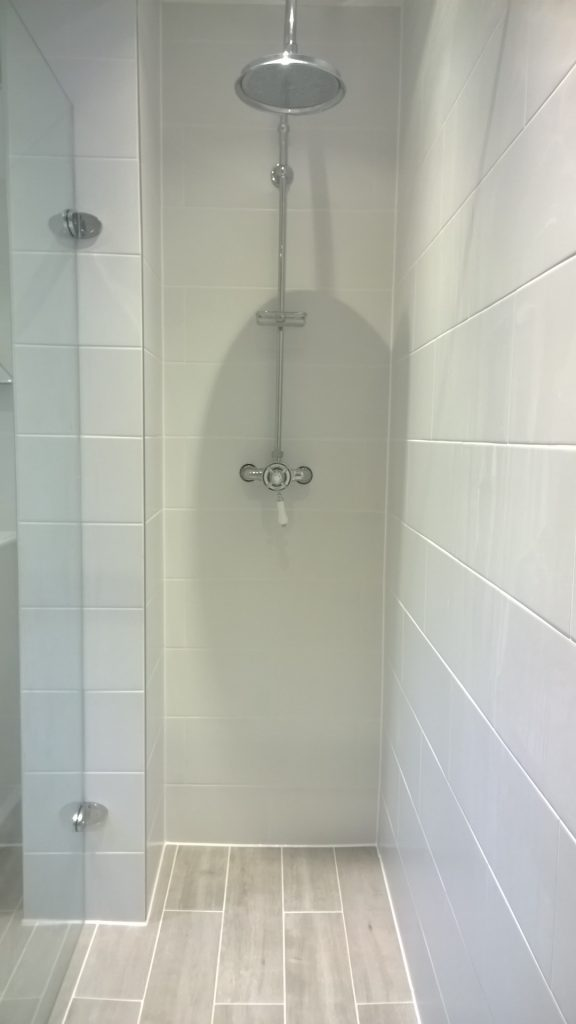 A wet room shower featuring a Burlington exposed shower valve and rigid riser