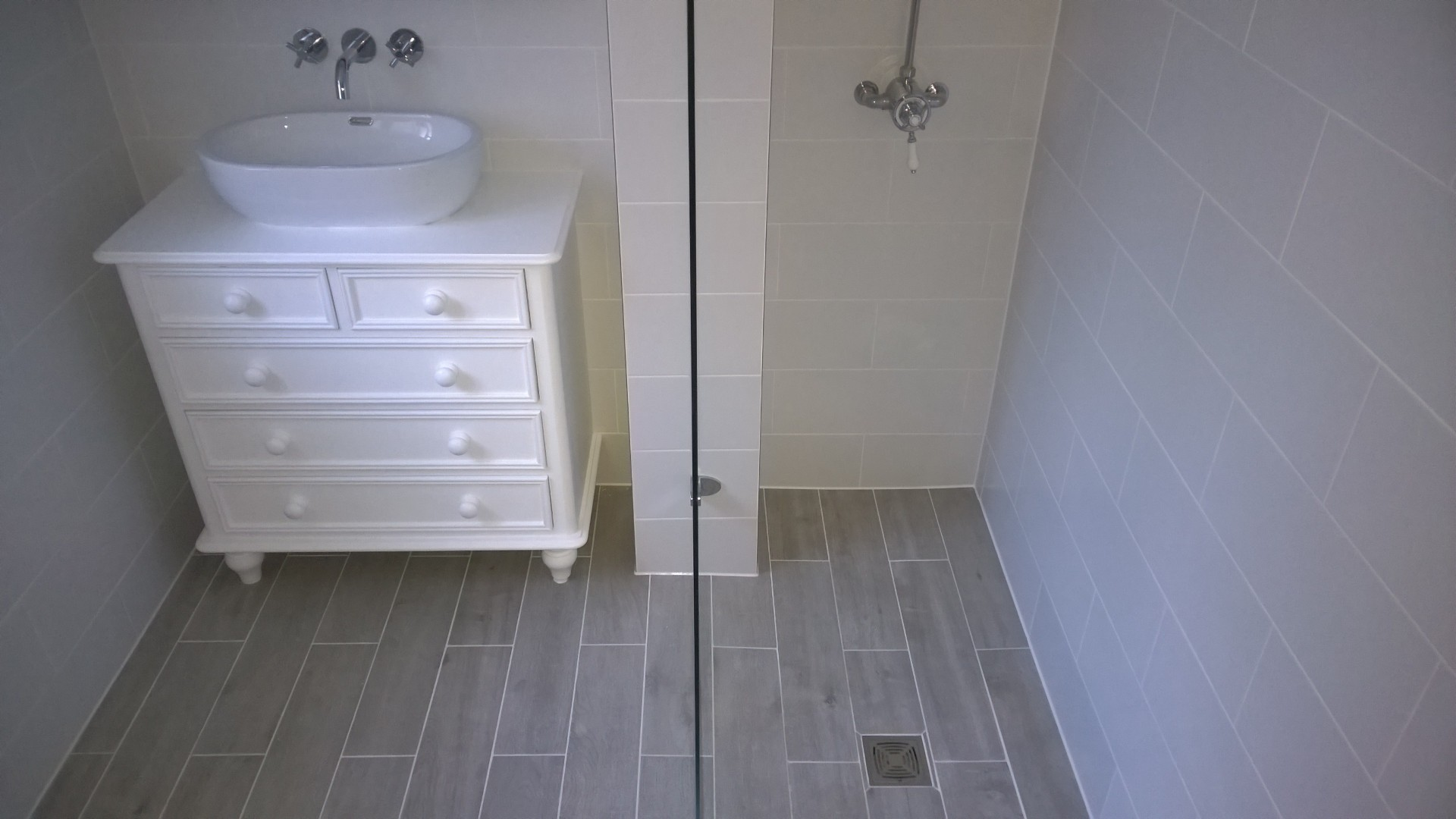 A wetroom shower with wood effect tiling and a vanity unit made from a reclaimed set of drawers