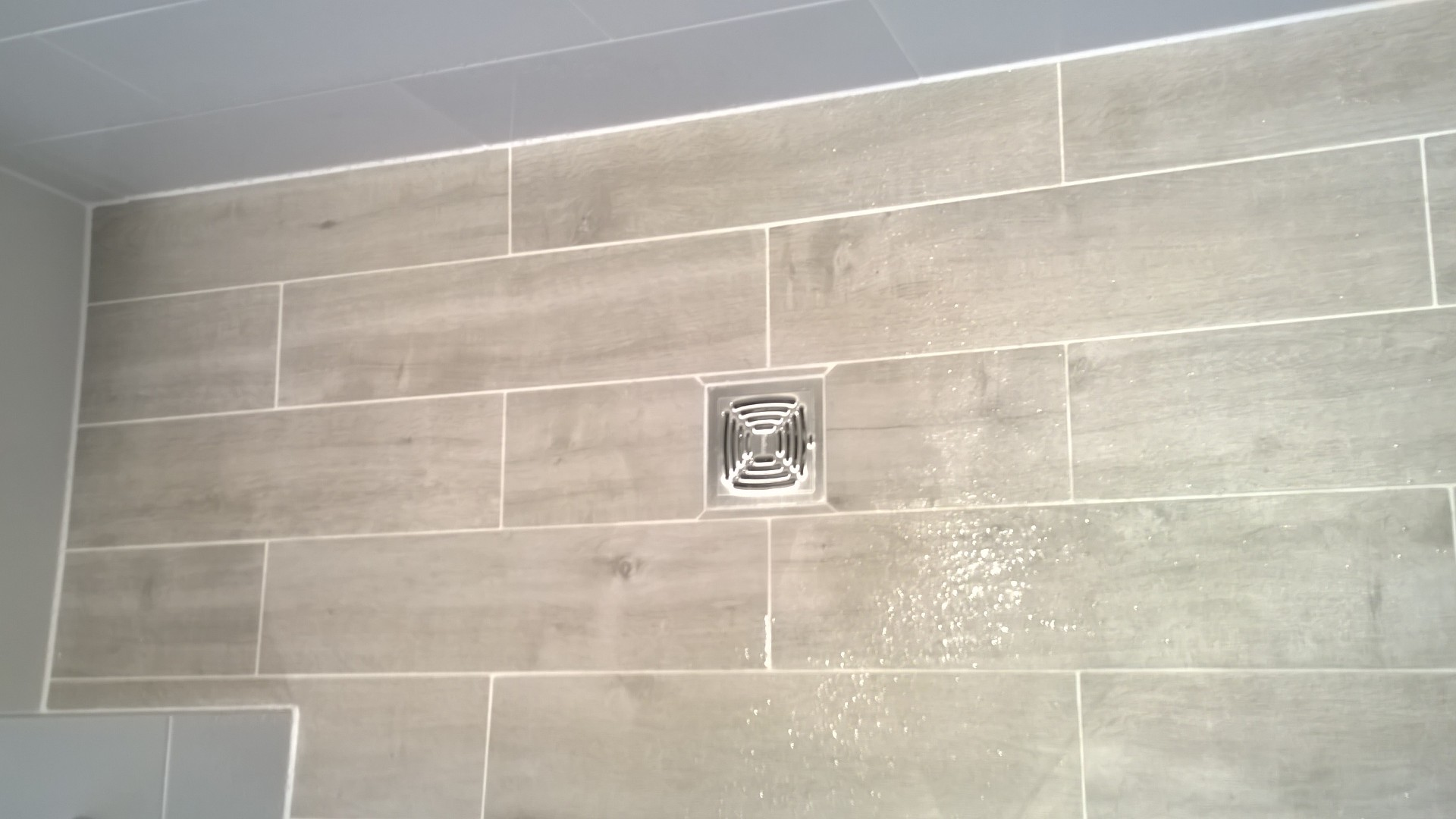 A wetroom floor using an impey aqua dec and wood effect porcelain tiles