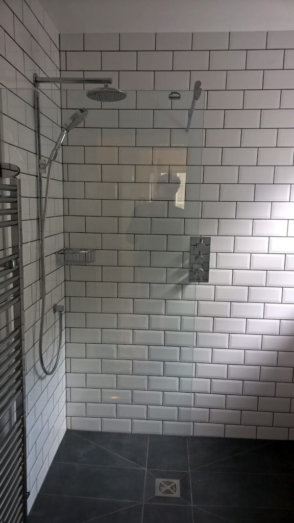 A wetroom shower with a recessed thermostatic valve, fixed head shower and handheld