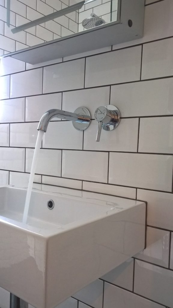 Picture of a wall mounted basin mixer and metro tiles