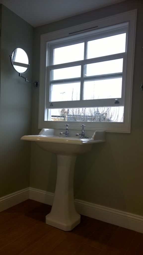 Traditional pedestal basin placed under a sash window with a pull out mirror