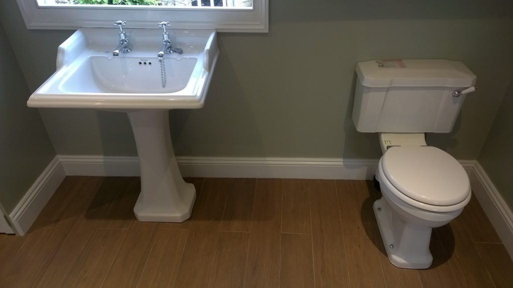 Picture of a bathroom with engineered wood flooring and traditional bathroom suite