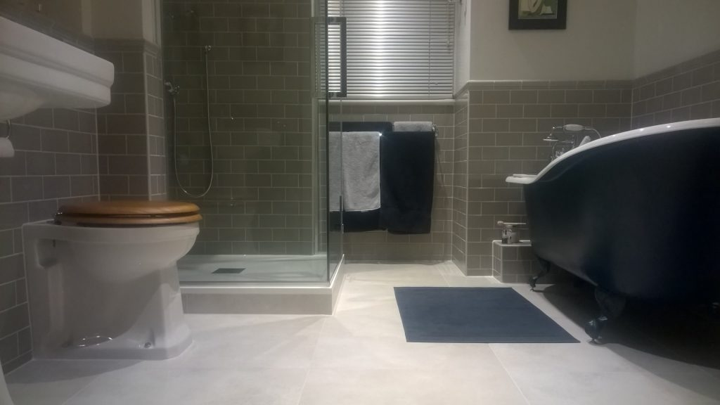 A bathroom with green metro wall tiles and matching dado rail
