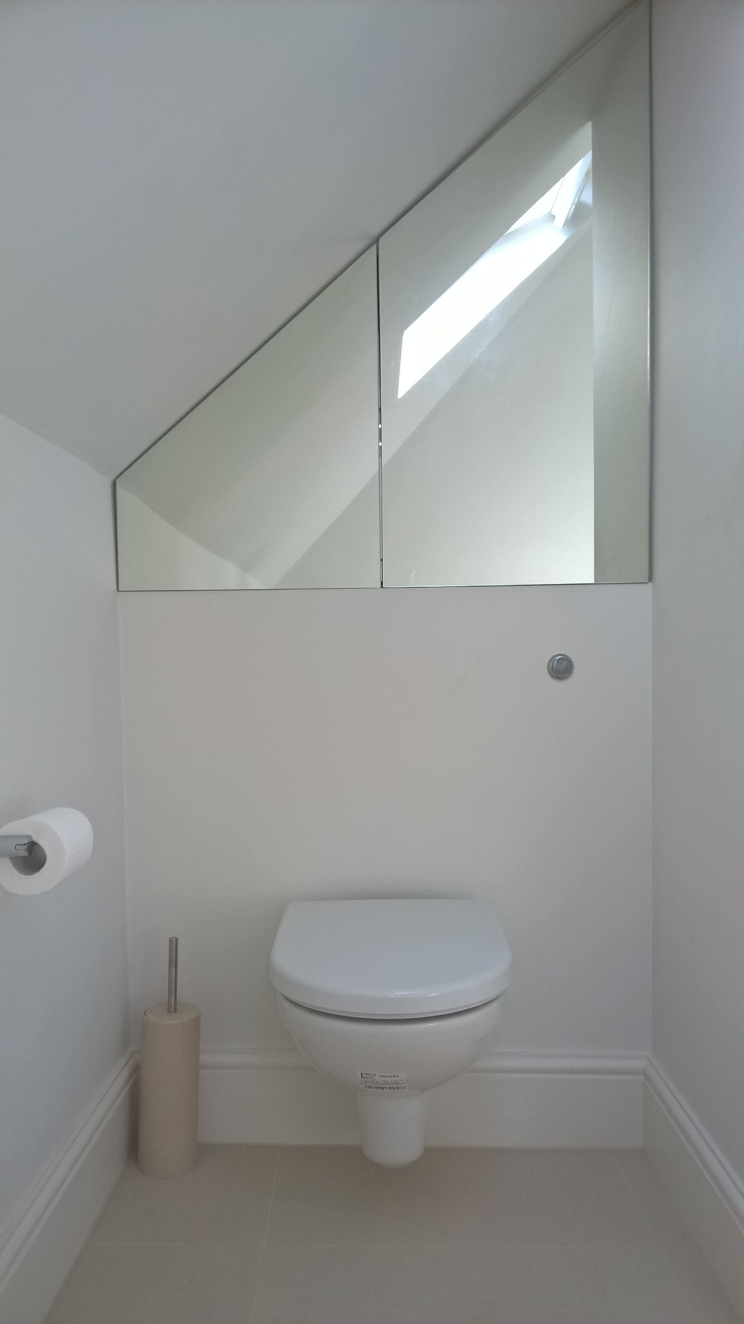 Bespoke mirror cabinets above a wall hung WC in an attic bathroom