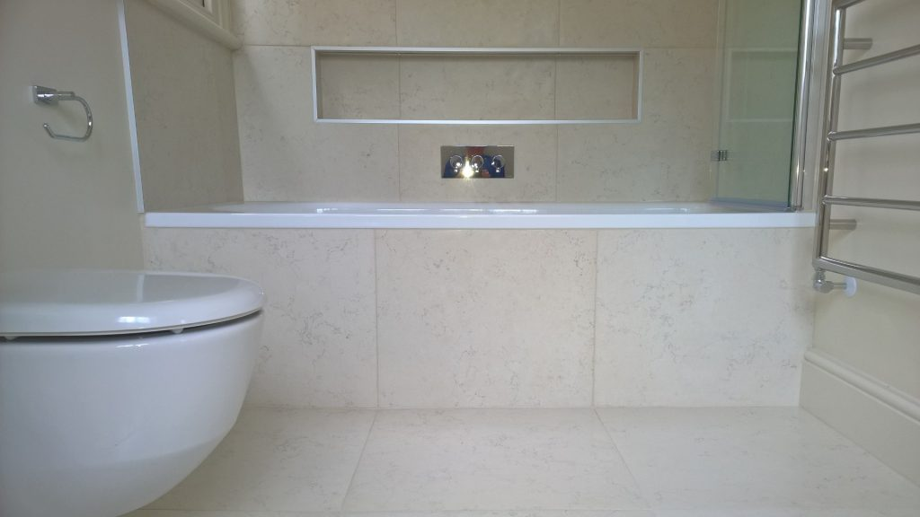 Steel bath with a tiled panel and recessed shelf