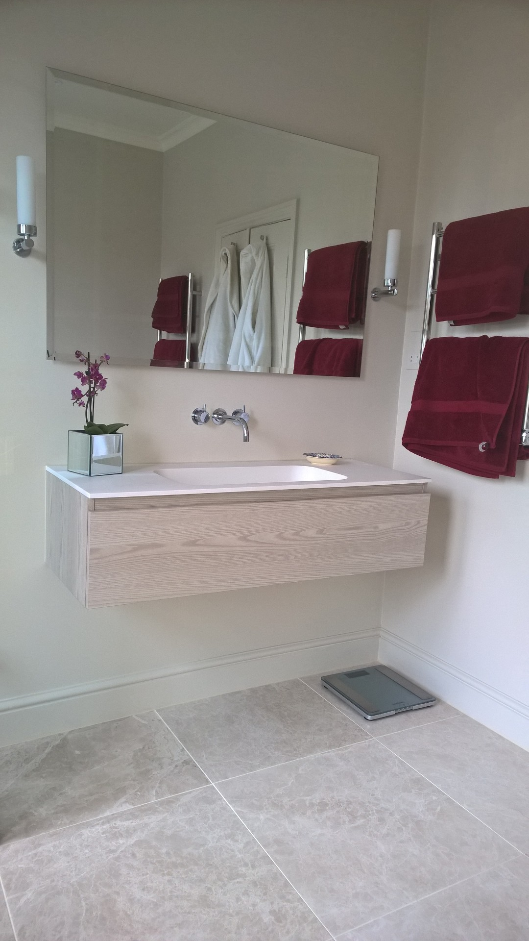 A wall hung basin unit with a mirror above and a heated towel rail